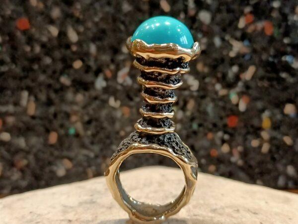 Photographie représentant une bague en or et argent oxydé avec turquoise.