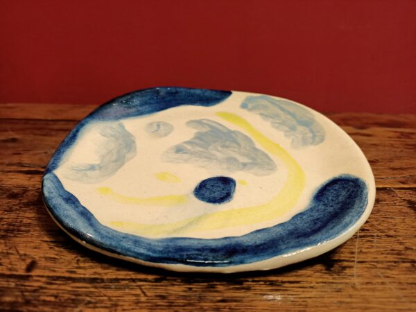 Glazed earthenware plate with bue and yellow designsdesigns.