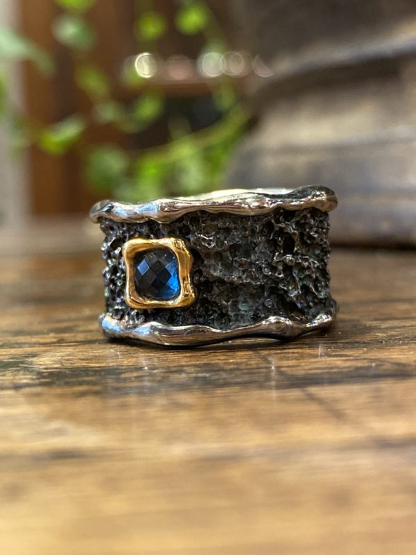 Photograph of a large oxidized and textured ring with a set blue topaz.