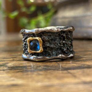 Photographie représentant un anneau large oxydé et texturé avec une topaze bleue sertie.