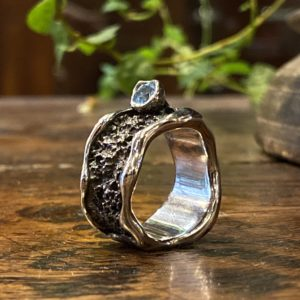 Photograph of a large oxidized and textured ring with a set light blue topaz.