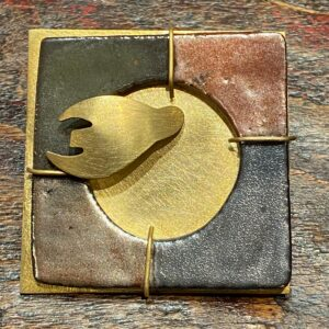 Enamelled stoneware and brass brooch.