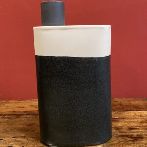 Object in the shape of a jerrycan in black and white porcelain.